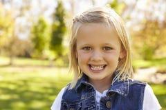 Menina loura idosa de cinco anos em um parque que sorri à câmera Fotos de Stock Royalty Free