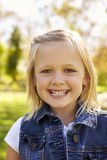 A menina loura idosa de cinco anos no parque sorri à câmera, vertical Foto de Stock