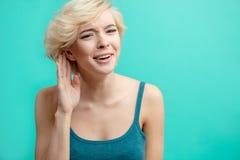 A menina loura impressionante está esticando suas orelhas enquanto quer conhecer a notícia a mais atrasada foto de stock