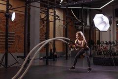 A menina loura impressionante séria é concentrada no exercício com cordas da batalha fotos de stock