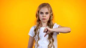 Menina loura infeliz que faz o gesto dos polegares-para baixo, serviços do desagrado, de má qualidade imagem de stock royalty free