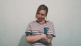 A menina loura irritada em camisa listrada com tatuagens amua na frente da parede branca filme