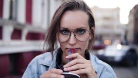A menina loura lindo com um dia claro compõe a vista da câmera, bebendo a bebida com uma palha e um sorriso desgastar filme
