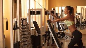 Menina loura lindo que pratica em um gym filme