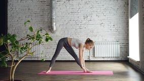 A menina loura magro nova está fazendo o complexo da ioga no estúdio com paredes brancas Está começando com as poses do guerreiro filme