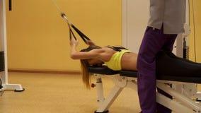 Menina loura magro que dá certo em um gym com treinador