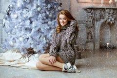 Menina loura muito bonita em um sittin feito malha da camiseta e das peúgas Imagem de Stock
