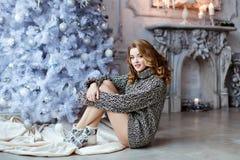 Menina loura muito bonita em um sittin feito malha da camiseta e das peúgas Foto de Stock
