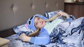Menina loura na cama na manhã em pijamas azuis video estoque