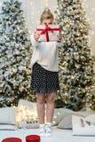 A menina loura na camiseta branca esconde a cara atrás do presente fotos de stock