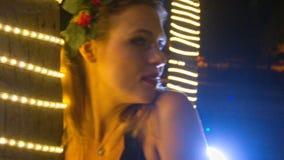 Menina loura na flor vermelha Garland Poses pela árvore na noite vídeos de arquivo