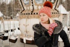 Menina loura na roupa tampão e mitenes vermelhos do inverno Caminhada no parque foto de stock royalty free