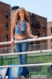 Menina loura nas calças de brim Fotografia de Stock Royalty Free