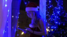 Menina loura no chapéu de Santa com uma tabuleta filme