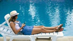 A menina loura no chapéu, macacões encontra-se pela associação e olha-se para telefonar vídeos de arquivo