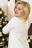 Menina loura no fundo da árvore de Natal Imagem de Stock Royalty Free