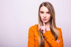 Menina loura no t-shirt alaranjado com gesto do silêncio no branco Fotos de Stock Royalty Free