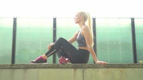Menina loura nova, atrativa e desportiva no sportswear que escuta a música e o relaxamento exteriores Cuidados médicos, esporte filme