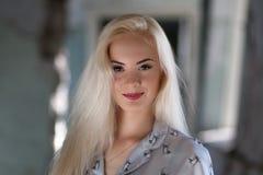 Menina loura nova bonita com uma cara bonita e sorriso bonito dos olhos O retrato de uma mulher com cabelo longo e surpresa olha fotografia de stock