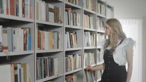 Menina loura nova bonita do estudante que toma o livro da prateleira na biblioteca video estoque