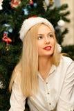 Menina loura nova bonita no chapéu vermelho de Santa no Natal fotos de stock royalty free