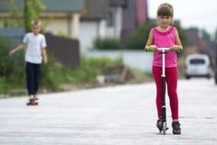 Menina loura nova bonito das crianças na roupa cor-de-rosa no 'trotinette' e no h Fotos de Stock Royalty Free