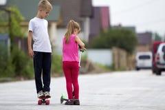 Menina loura nova bonito das crianças na roupa cor-de-rosa no 'trotinette' e no h Foto de Stock Royalty Free