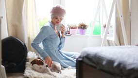 Menina loura nova com o cão que senta-se em um assoalho filme