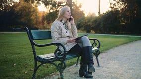 Menina loura nova com o tablet pc e o telefone celular que sentam-se no banco de parque video estoque