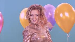 A menina loura nova comemora o aniversário Mas está vestindo um vestido brilhante bonito Perto dos balões vídeos de arquivo