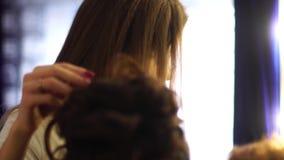A menina loura nova do estilista faz o penteado a uma mulher video estoque