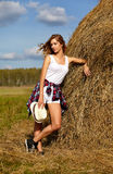 Menina loura nova do país no chapéu perto do monte de feno foto de stock
