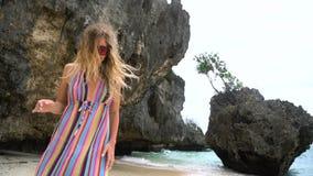 A menina loura nova em um vestido brilhante corre ao longo da praia branca, sorrindo na câmera, desenvolvendo o cabelo filme