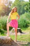 Menina loura nova em uma blusa amarela com uma saia cor-de-rosa brilhante que levanta em um parque do verão nos raios de um sol b Fotos de Stock