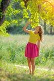 Menina loura nova em uma blusa amarela com uma saia cor-de-rosa brilhante que levanta em um parque do verão nos raios de um sol b Fotografia de Stock
