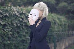 Menina loura nova que descola uma máscara Fingimento ser alguma outra pessoa conceito outdoors Fotografia de Stock