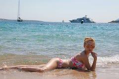 menina loura nova que encontra-se no mar com um fundo branco do iate imagem de stock