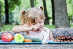 Menina loura nova que escolhe o alimento para sua refeição foto de stock