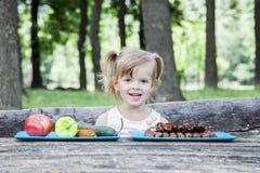 Menina loura nova que escolhe o alimento para sua refeição imagens de stock royalty free