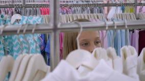 Menina loura nova que escolhe a roupa elegante no boutique video estoque