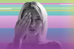 Menina loura nova que fecha um olho e que verifica sua visão fotografia de stock royalty free
