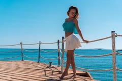 Menina loura nova que levanta no cais com fundo do seascapeon imagem de stock royalty free
