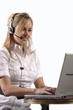 Menina loura nova que trabalha no portátil com auriculares Imagens de Stock Royalty Free