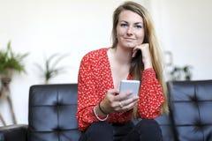 Menina loura nova que usa um smartphone ao sentar-se no sofá de couro fotos de stock