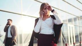 A menina loura nova quente presumido está pelo terminal de aeroporto, fala em seu telefone, verifica o tempo, toca nela vídeos de arquivo