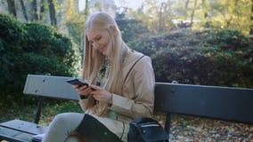 A menina loura nova usa um telefone celular em um banco no parque fora vídeos de arquivo