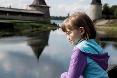 A menina loura olha o rio Foto de Stock