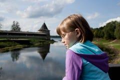 A menina loura olha o rio Imagens de Stock