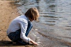 A menina loura olha o rio Imagem de Stock
