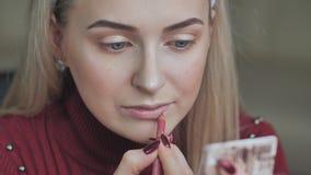 Menina loura para aplicar o batom com o lápis cosmético nos bordos video estoque